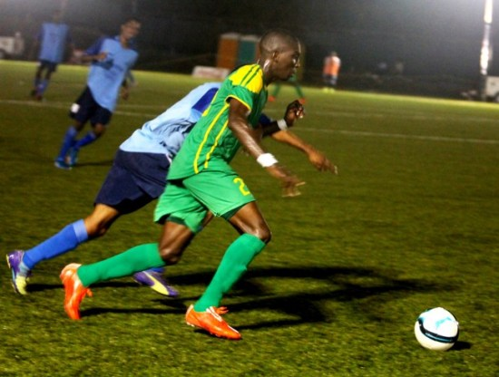 BDFSP captain Romario Harewood goes after the ball while Notre Dame's striker Dwayne Mars puts pressure on  him.