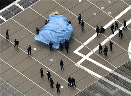 Investigators gathering around a small drone covered with blue sheets, on the roof of Prime Minister Shizo Abe's official residence in Tokyo today.