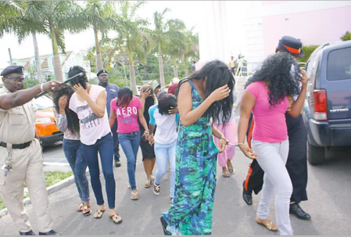 Police officers escorting Jamaican and Bahamian females to court yesterday to be charged with committing grossly indecent acts.