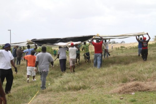 Some of the men in the community making their way with the huge kite  to hoist it.