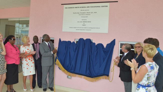 At left, Prime Minister Freundel Stuart (fifth from left) and benefactor Derrick Smith (fifth from right) unveiling plaque as Minister of Education Ronald Jones (fourth from left) and other officials look on.