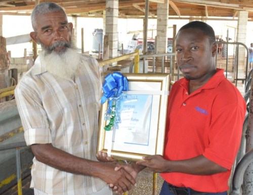 Farmer Barry Bishop receiving his certificate of recognition  for having the Best Overall Milk Quality from Lorenzo Roach,  Pine Hill Dairy daily operations manager.