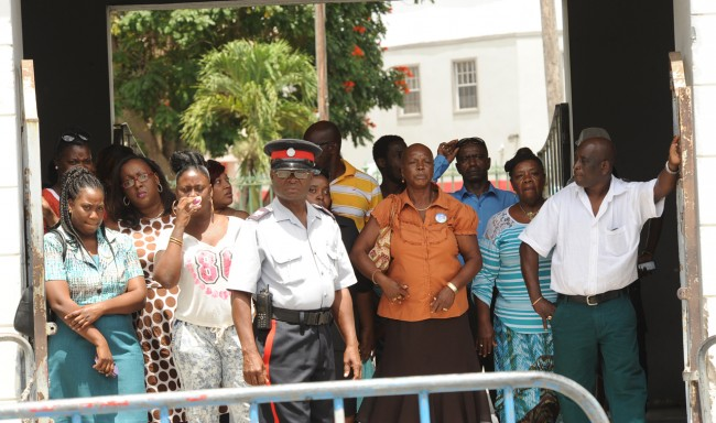 Family and friends of Selwyn Knight and onlookers, including widow Marlene (centre) behind the police barricade as they await the arrival  of Constable Everton Gittens.