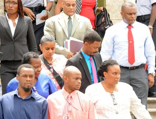Constable Everton Gittens (centre) leaves the court surrounded by colleagues and members of his legal team.