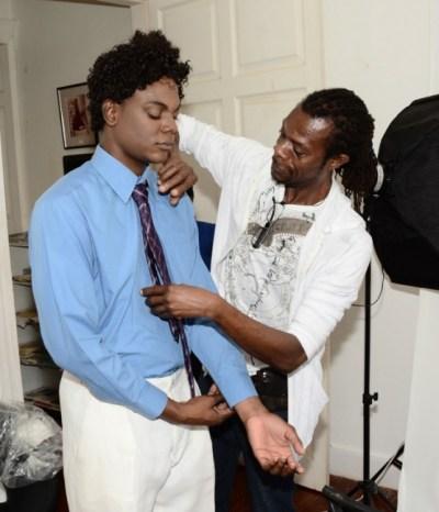 Wardrobe master Glenn Brathwaite making  last-minute adjustments to the wardrobe of actor Angelo Lascelles, who portrays National Hero Clement Payne.
