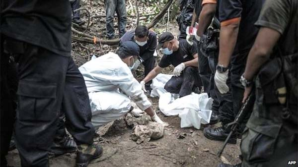 A Royal Malaysian Police forensic team handles exhumed human remains in a jungle at Bukit Wang Burma in the Malaysian northern state of Perlis, which borders Thailand, on Tuesday