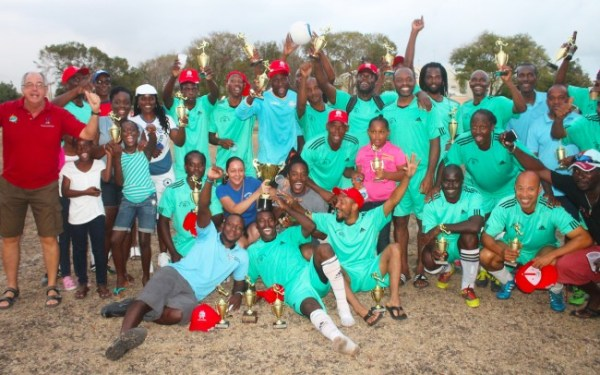 Champions of the 2015 Banks International Masters Football Festival, Wildey, celebrate with supporters.