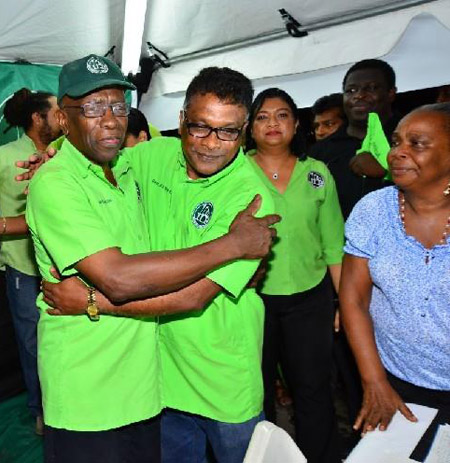 Independent Liberal Party (ILP) supporters greet their leader Jack Warner at a meeting at the corner of Endeavour Road and Egypt Village, Chaguanas last night..