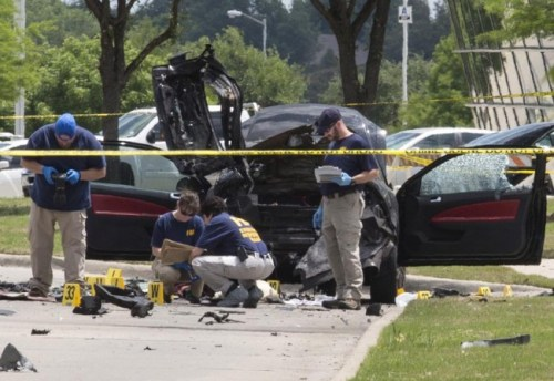 Local police and FBI investigators collect evidence and survey the scene where two gunmen were shot dead, after their bodies were removed in Garland, Texas.
