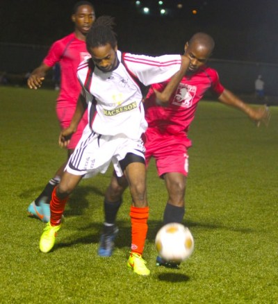 Renaldo Marquez (right)  and T-shane Lorde (left) of Gall Hill put pressure on Brittons Hill danger man  Dwayne Stanford.