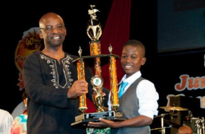 Reigning eight-to-12 Junior Monarch  Ranaan Hackett receiving his trophy  from Minister of Culture Stephen Lashley at last year's Finals.