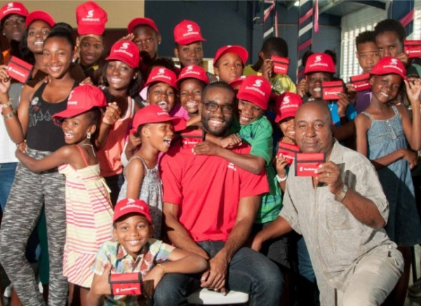 Ryan Bascombe, personal banking officer  of Scotiabank being swarmed  by the Junior Calypso Monarch entrants  after his presentation at the first recent workshop. At right is mentor and musican Anthony Sargeant.