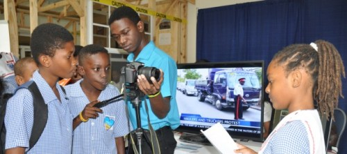 People's Cathedral student Anisa Watts (right) playing the role of a news anchor, as her classmate Sylvan Wade (second from left) focuses on her with assistance from Junior Information Technology Officer Stefon Jordan (third from left) at the Barbados TODAY Booth.