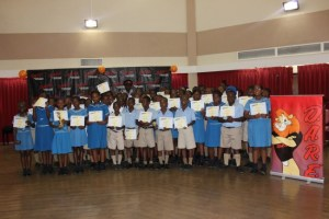 Sergeant Roland Cobbler, who is in charge of the DARE programme in Barbados (standing behind the students), with participants of Wilkie Cumberbatch Primary School.