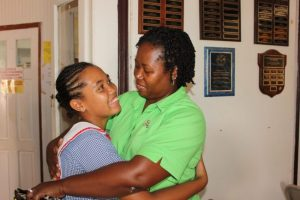 Naleena Gaskin, top performing 11-Plus student of The Rock Christian School,  being congratulated by mum Dawn-Dew Thompson.