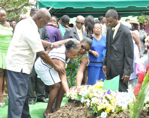 A tearful Julianne Weekes receiving support from loved ones as she laid  a wreath on her son's grave.