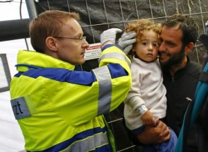 A doctor examining newly arrived migrants at an improvised temporary shelter in a sports hall  in Hanau, Germany, today.