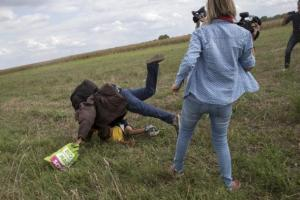 A migrant carrying a child fell after tripping on a TV camerawoman (right) while trying to escape from a collection point in Roszke village, Hungary, yesterday.
