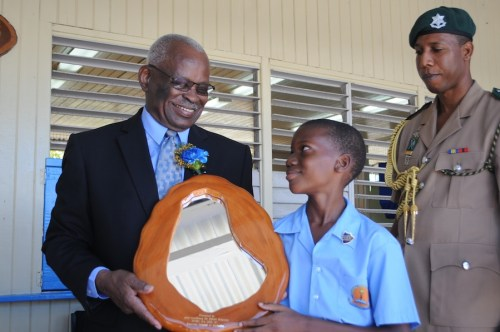 Governor General Sir Elliott Belgrave (left) accepting a gift from Vauxhall Primary School head boy Shaquon Walthrust (centre) as aide-de-camp Ashton Caddle looks on.