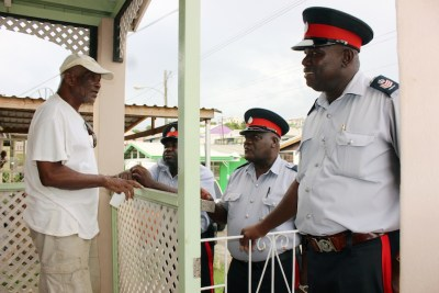 Station Sergeant O'Neal Small, (right) having a word with senior citizen Livingstone Forde of Lettuce Lane,  Grazettes, St Michael.