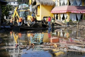 People work on removing the debris of houses and shops destroyed by waves after an earthquake hit areas of central Chile, in Concon city, northwest of Santiago, today.
