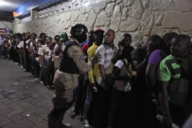 A National Police officer pushes a voter back in line during national elections in the Petion-Ville suburb of Port-au-Prince, Haiti, Sunday, Oct. 25, 2015. The country is holding the first-round presidential vote Sunday along with balloting for numerous legislative races and local offices. (AP Photo/Ricardo Arduengo)
