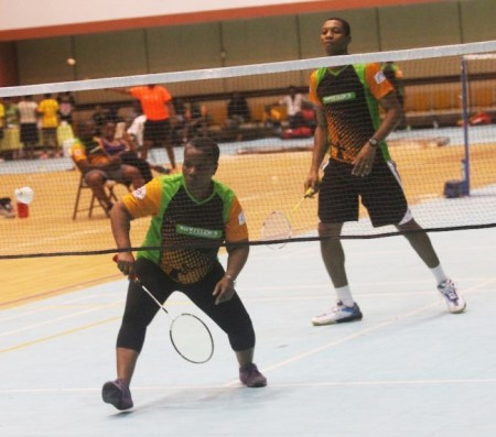 Beverley Harding of the victorious Shuttlers C team looks determined to defend a ball while teammate Athelston Forde waits in anticipation.