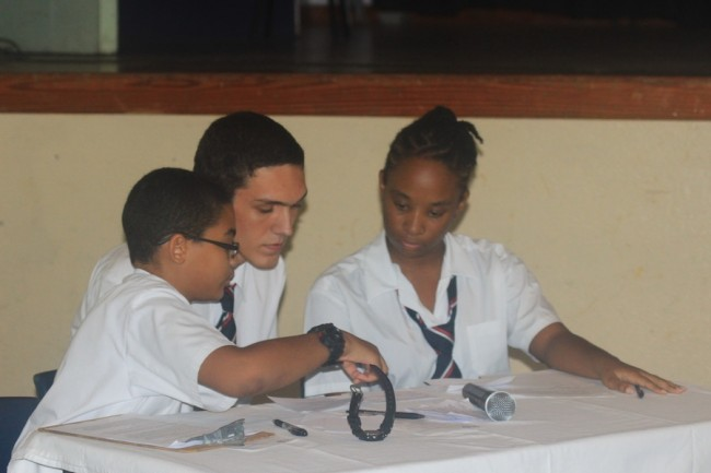 Members of the opposition team (From left) Khaleel Kothdiwala, Brandon Boras and Destini Watson deliberating during the debate.
