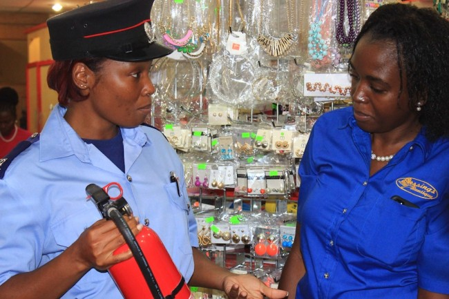Fire Prevention Officer, Natasha Forde (left) explains how a fire extinguisher is used, while manager of  Blessings Boutique, Deidre Thorne, listens intently.