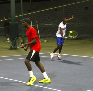 Kevin Yarde plays a backhand shot while teammate Brandon Lee waits in anticipation of his play.