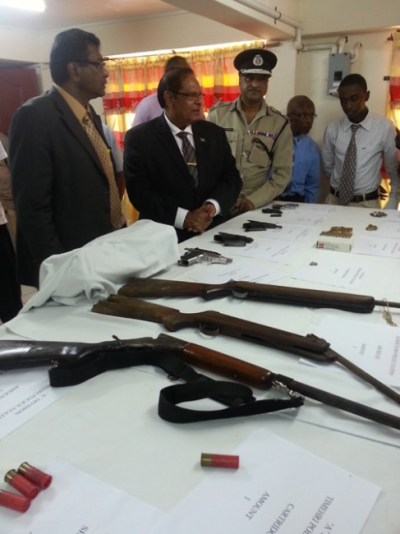 Minister of Public Security Khemraj Ramjattan, Prime Minister Moses Nagamootoo and Police Commissioner Seelall Persaud examining illegal weapons that were turned in last month.
