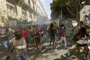 Protesting university students fleeing as police fire stun grenades outside Parliament in Cape Town, South Africa, today.