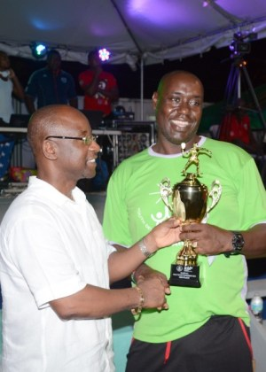 Roger Daniel (right) takes the second-place trophy in the in-house competition from Minister of Sports Stephen Lashley.