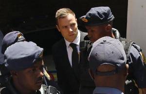 South African Olympic and Paralympic sprinter Oscar Pistorius being escorted to a police van after his sentencing at the North Gauteng High Court in Pretoria October 21, 2014.