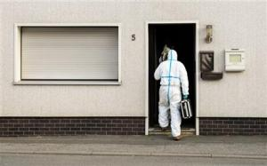 A police investigator in protective cloth entering a house in Wallenfels, southern Germany, this morning where police found bodies of multiple babies.