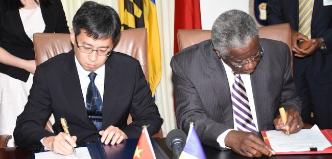 Prime Minister Freundel Stuart (right) and the Deputy General Manager of the Concessional Loan Department of the Exim Bank, Tong Qing, signing the loan agreement.