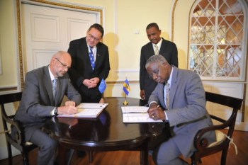 European Union ambassador to Barbados and the Eastern Caribbean Mikael Barfod and Prime Minister Freundel Stuart sign the deal as representatives from their respective delegations look on.