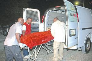 Mortuary services personnel removing the body of Joyell McIntosh.