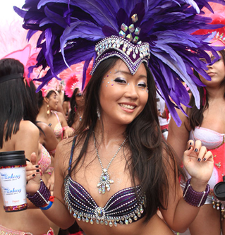 A reveller from the band Fantasy Carnival smiling for a photograph while parading on Carnival Tuesday in Port-of-Spain.