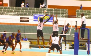 Barbados captain Andriy Stapleton (right) evades the Trinidadian blocks with this spike. (Picture by Morissa  Lindsay)
