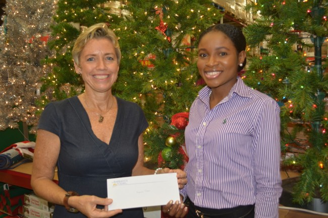 Virginia Foster accepting her  $1000 shopping spree voucher from Account Executive Omisa Hobbs.