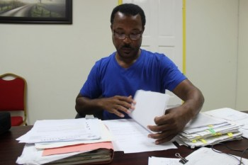 Horace Drakes sifting through legal and contractual documents acquired over an 11-year period.