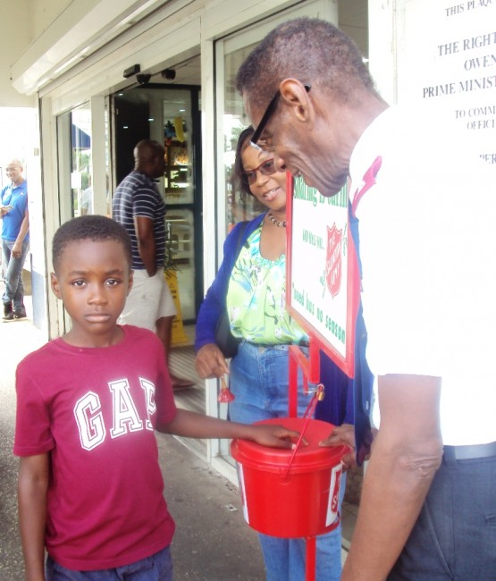 Never too young to start giving - Major Denzil Walcott and volunteer Eugenia Edey encourage this little one to give