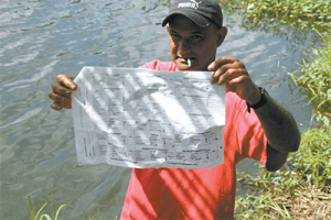 Ronnie Ramdeen showing United National Congress election papers which were found at Petrotrin's Katwaroo Dam, Katwaroo Trace, Penal, yesterday.