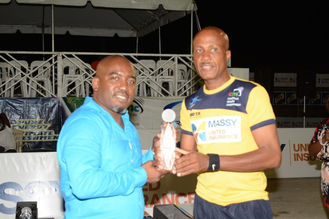 Veterans champion Rodney Lorde (right) accepting his trophy from CEO of the PRTA Dale Clarke.