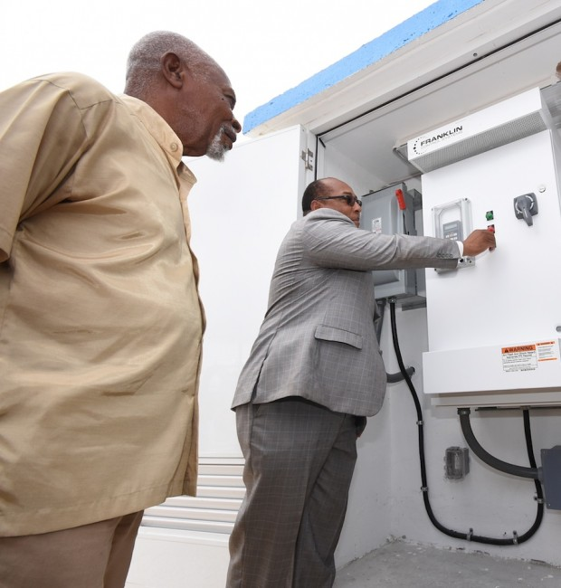 BWA Chairman Atlee Brathwaite (left) looks on as Minister Dr David Estwick presses the  button giving residents greater access to drinking water from the Groves Pumping Station in St Philip.