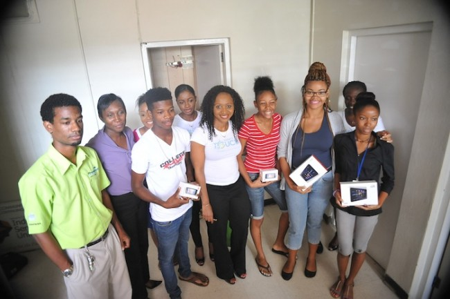 Some of the second year mass communications students and their tutor Wendy Cox (second from left) showing off their special gifts,compliments FLOW and Promotech, represented here by Akira Joseph (left).