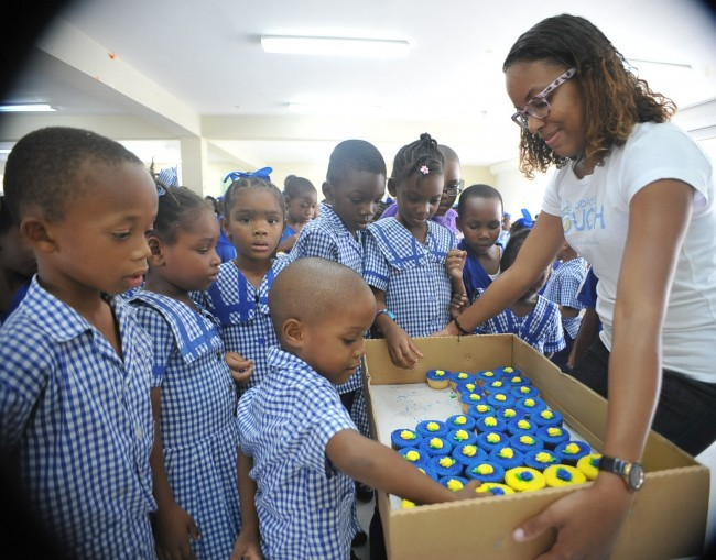 BT Marketing Executive Tamesha Doughty sharing out cupcakes to the students at George Lamming Primary.