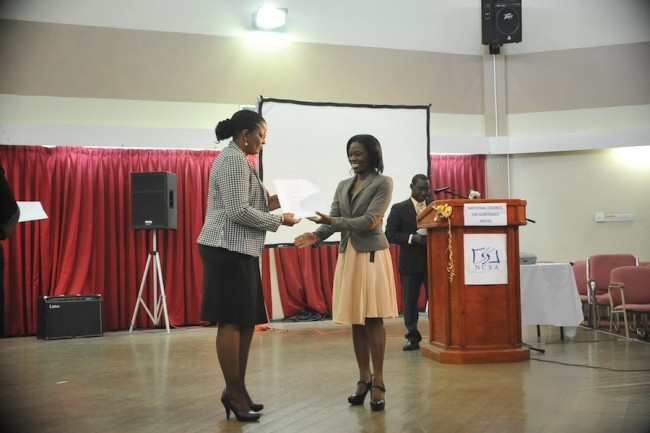 Tutor in the programme, Paulavette Atkinson (right), receiving an award from NCSA acting manager Betty Hunte.