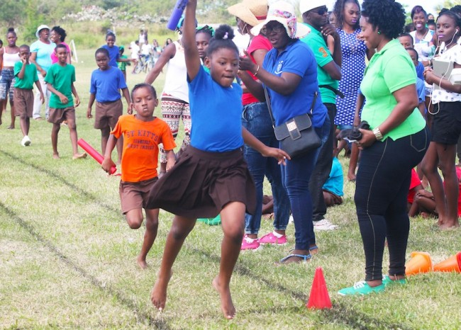 Dashra Hunte of Blue House raises her hand in triumph as she anchors them to victory in the under-11 girls 4x100m relay ahead of Tameisha Waldron of Red House.